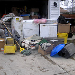 Soaked, wet personal items sitting in a driveway, including a washer and dryer in Logansport.
